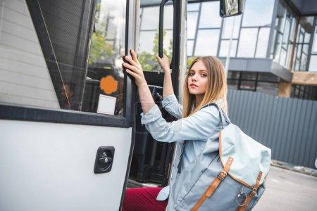 Foto de Atractivos turísticos mujer joven con mochila en el autobús del recorrido en la calle urbanita - Imagen libre de derechos
