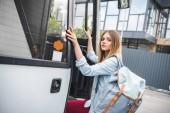 """Постер, картина, фотообои """"привлекательный молодой женщины турист с рюкзаком, войдя в автобус путешествия на городской улице"""""""