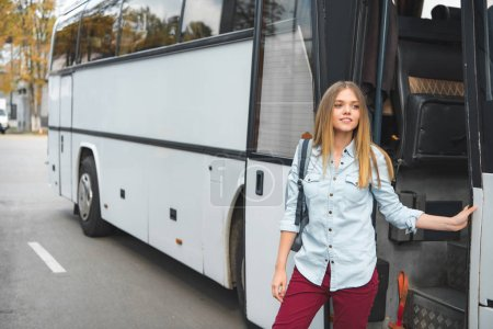 Photo for Young woman with rucksack standing near travel bus at street - Royalty Free Image