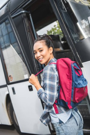 Photo for Selective focus of asian female tourist with backpack looking at camera near travel bus at city street - Royalty Free Image