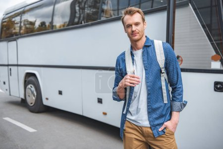 Photo for Adult man with backpack posing near travel bus at street - Royalty Free Image