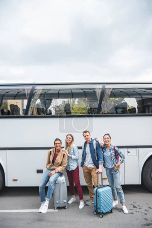 Photo for Young multicultural friends with wheeled bags posing near travel bus at street - Royalty Free Image