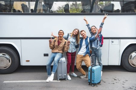 cheerful multiethnic tourists with travel bags doing peace signs near bus at street