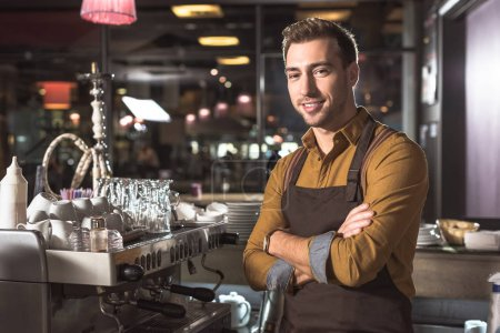 Photo for Handsome young barista with crossed arms standing near coffee machine and looking at camera - Royalty Free Image