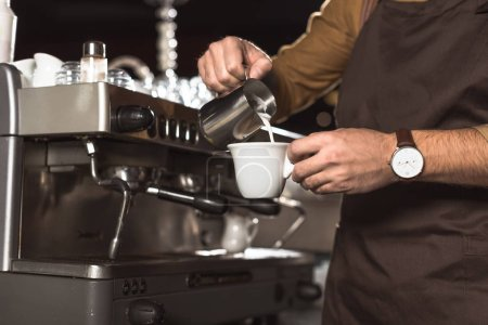cropped shot of barista pouring milk into coffee while preparing it in cafe