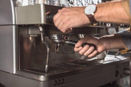 cropped shot of barista using coffee machine in restaurant