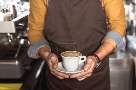 cropped shot of barista in apron holding cup of fresh made cappuccino