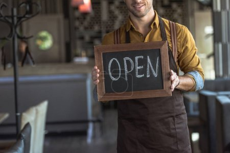 cropped shot of smiling young waiter holding board with open inscription in cafe