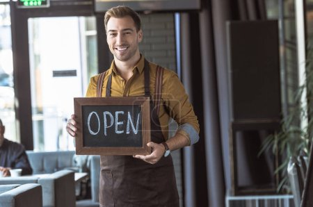 handsome young waiter holding board with open inscription in cafe