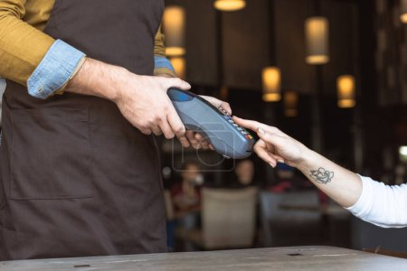 cropped shot of waiter holding payment terminal while female client entering pin in cafe