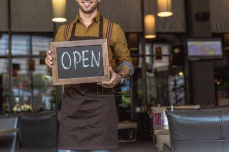 Photo pour Plan recadré de serveur heureux tenant tableau noir avec inscription ouverte dans le café - image libre de droit
