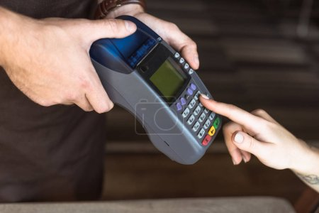 cropped shot of waiter holding payment terminal while customer entering pin in cafe