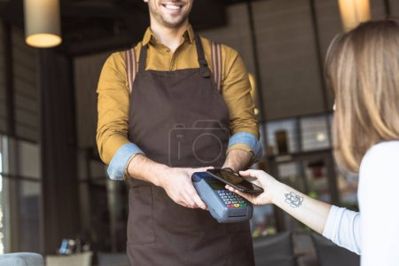 Photo for Cropped shot of smiling waiter holding payment terminal while customer doing contactless purchase with smartphone in cafe - Royalty Free Image