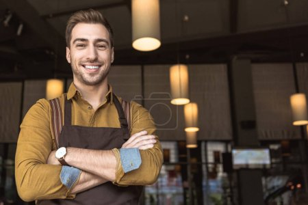 Photo for Smiling young waiter with crossed arms looking at camera in cafe - Royalty Free Image