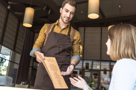 Photo for Happy young waiter showing menu list to female customer in cafe - Royalty Free Image