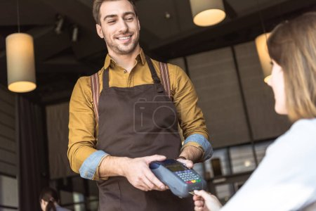 happy young waiter holding payment terminal while client inserting credit card