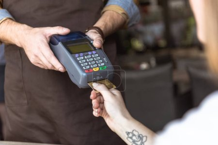 cropped shot of waiter holding payment terminal while customer inserting credit card