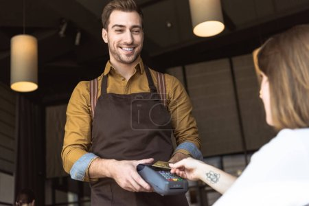 smiling young waiter holding payment terminal while customer doing contactless purchase with credit card in cafe