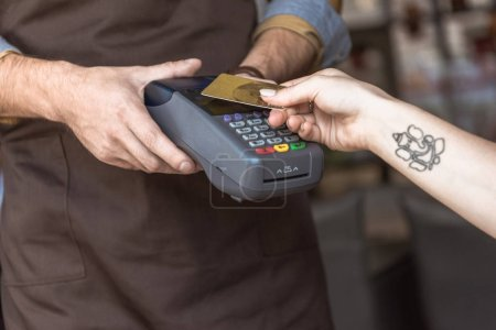 cropped shot of waiter holding payment terminal while customer doing contactless purchase with credit card in cafe