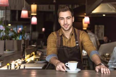 Photo for Attractive young barista with cup of delicious coffee looking at camera - Royalty Free Image
