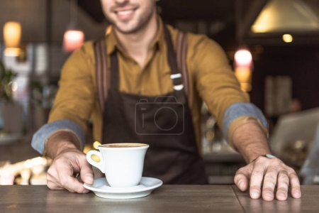 cropped shot of young barista with cup of delicious coffee
