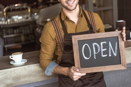 cropped shot of happy young waiter holding chalkboard with open inscription in cafe