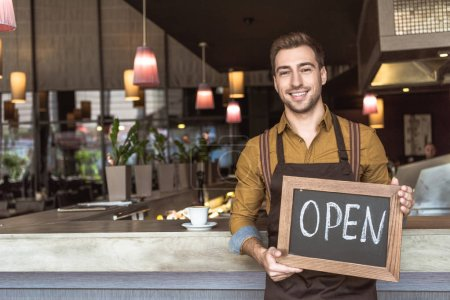 happy young waiter holding chalkboard with open inscription in cafe