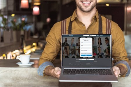cropped shot of smiling young waiter holding laptop with linkedin website on screen in cafe