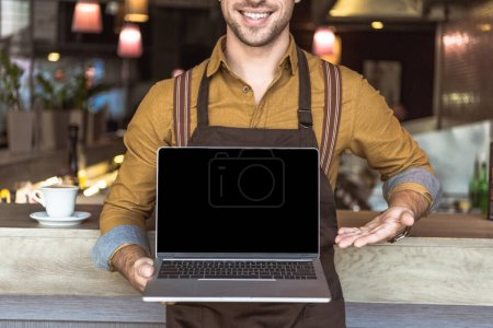 Photo for Cropped shot of smiling young waiter holding laptop with empty screen in cafe - Royalty Free Image