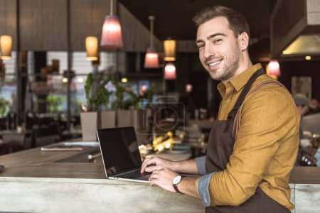 handsome young waiter using laptop a bar counter in cafe