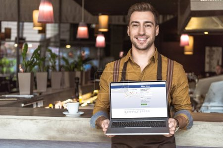 handsome young waiter holding laptop with facebook website on screen in cafe