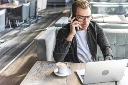Photo pour Attrayant jeune pigiste travailler avec ordinateur portable et parler par téléphone dans le café - image libre de droit