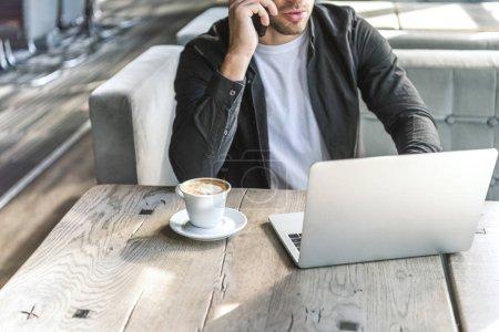 Foto de Foto recortada de jóvenes freelance trabajando con ordenador portátil y hablando por teléfono en el restaurante - Imagen libre de derechos