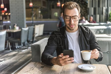 attractive young man with cup of coffee using smartphone in cafe
