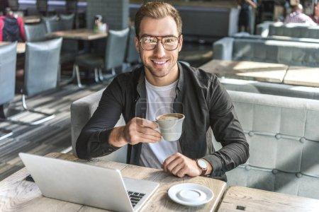 Photo pour Beau jeune pigiste avec tasse de café et ordinateur portable regardant la caméra dans le café - image libre de droit