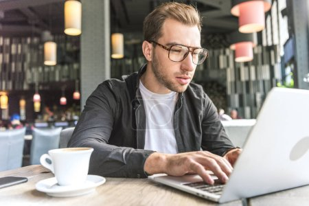 concentrated young freelancer with cup of coffee working with laptop in cafe