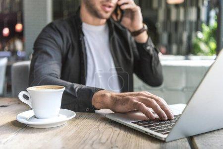 Photo pour Plan recadré de jeune pigiste avec tasse de café travaillant avec ordinateur portable dans le café et parlant par téléphone - image libre de droit