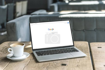 Photo for Cup of coffee and laptop with google website on screen on rustic wooden table at cafe - Royalty Free Image