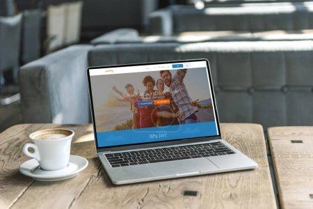 Photo pour Tasse de café et portable avec le site de couchsurfing à l'écran sur une table en bois rustique au café - image libre de droit
