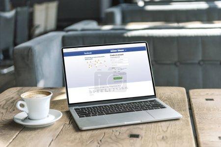 Tasse Kaffee und Laptop mit Facebook-Website auf dem Bildschirm auf rustikalem Holztisch im Café