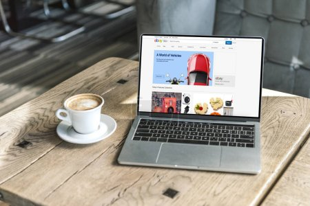 cup of coffee and laptop with ebay website on screen on rustic wooden table at cafe