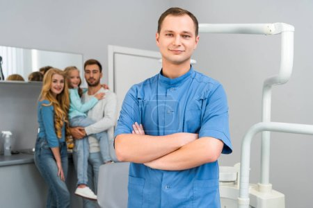 Photo for Handsome young dentist with crossed arms looking at camera while young family standing on background together - Royalty Free Image