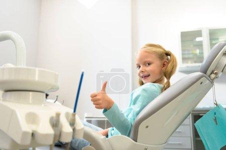 Photo pour Heureux petit enfant assis dans un fauteuil dentaire au cabinet dentiste et montrant le pouce vers le haut - image libre de droit