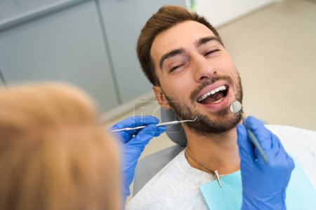 cropped shot of female dentist examining teeth of handsome happy client