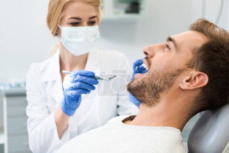 young female dentist examining teeth of handsome smiling client in dental chair