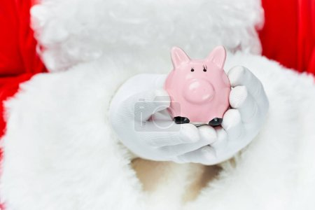 cropped view of santa claus holding piggy bank