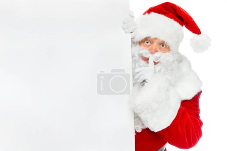 Photo for Santa claus with blank placard showing silence symbol isolated on white - Royalty Free Image