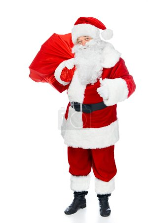 Photo for Santa claus with red christmas bag showing thumb up isolated on white - Royalty Free Image