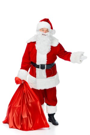 santa claus with red christmas bag showing something isolated on white