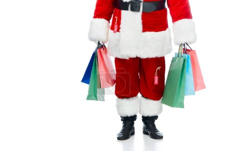 low section of santa claus in red costume with sale tags holding shopping bags isolated on white